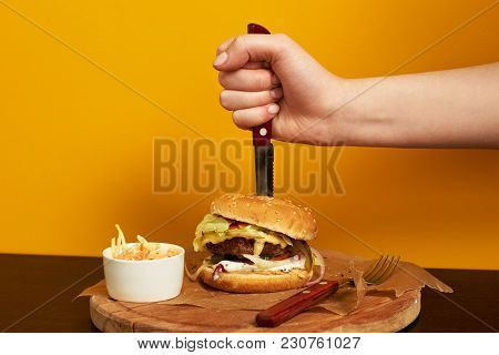 Hand Stabbing With Knife Burger Lying With Portion Of Salad And Fork On Round Wooden Plate Covered W