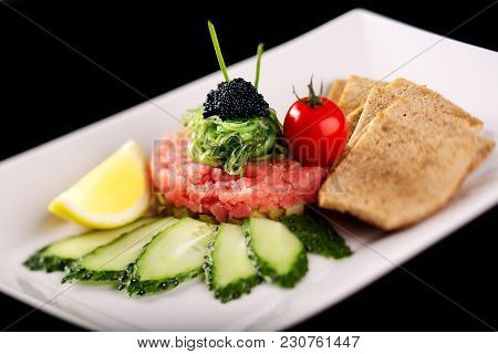 On A White Plate Tartare With Tuna And Gherkins. Decorated With Fresh Cherry Cucumbers And Lemon. Al