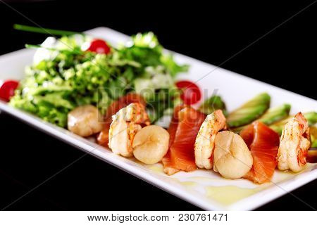 On A White Plate A Mix Of Salad With Slices Of Salmon Shrimps And Sea Buckets. Decorated With Avocad