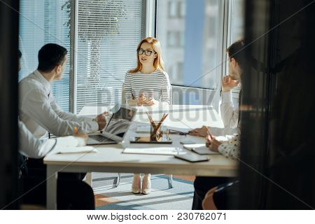 Important Talk. Charming Young Female Boss Sitting At The Head Of The Table Next To Her Employees An