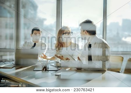 Discussing Enthusiastically. Charming Young Woman And Two Male Colleagues Sitting At The Table And H