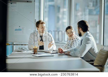 Nice Start Of Day. Lively Young Colleagues Sitting At The Table And Laughing Cheerfully, Joking Whil