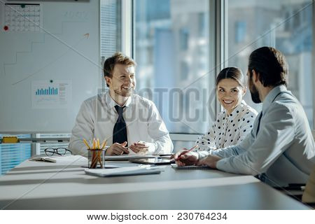 Pleasant Conversation. Upbeat Young Colleagues Sitting At The Table During The Meeting And Chatting