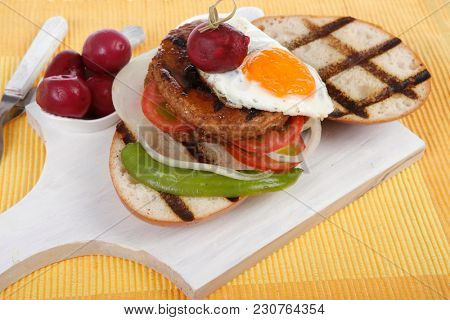 junk food meat big beef hamburger fried eggs on white wood plate with cutlery ketchup sauce and pickels on yellow mat isolated over white background
