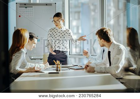 Good Psychologist. Pleasant Young Female Boss Having A Meeting With Her Employees And Trying To Solv