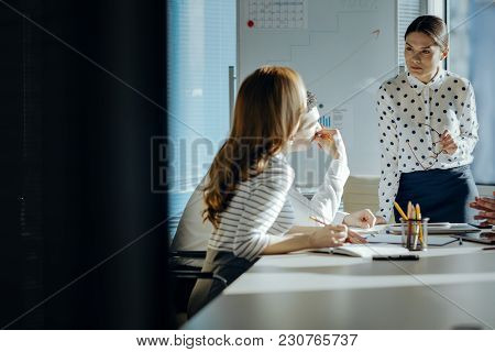 Paying Attention. Pleasant Young Woman Standing At The Head Of The Table And Listening Attentively T