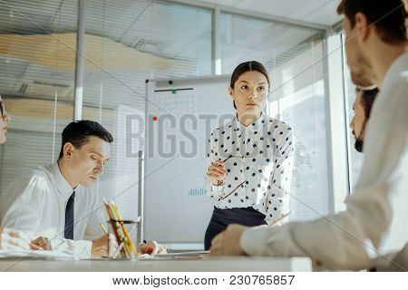 Important Staff Survey. Pleasant Female Boss Conducting A Daily Meeting With Her Colleagues And List