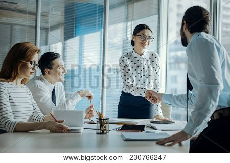 Business Etiquette. Charming Young Businesswoman Shaking Hands With Her Male Colleague While Having