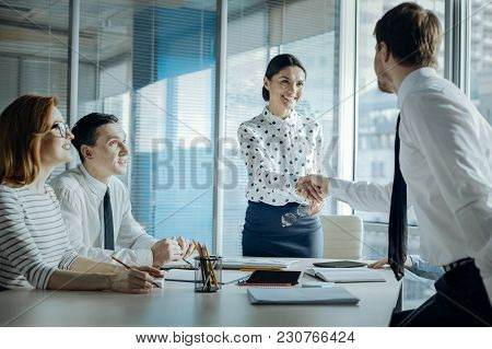 Successful Negotiations. Beautiful Young Businesswoman Giving A Handshake To One Of Her Business Par