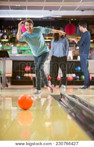Confident young man throwing ball in bowling club with friends talking in background
