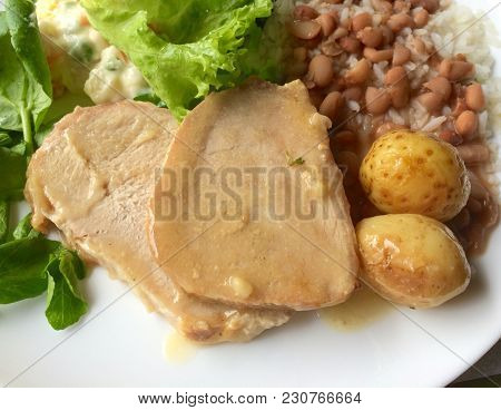 Slices Of Roasted Pork Tenderloin With Rice, Beans And Salad