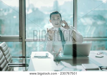 Crucial Discussion. Charming Young Man Sitting At The Table In His Office With Big Windows And Negot