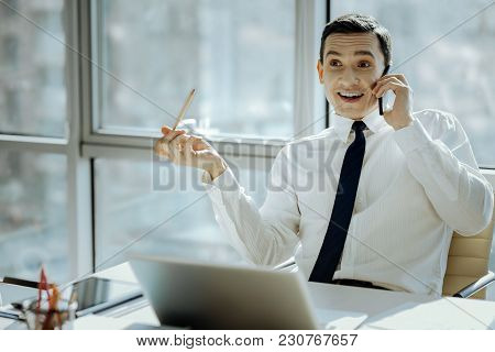 Great News. Charming Young Man Sitting At The Table In His Office And Smiling Widely, Being Pleasant