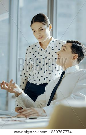 Feedback Needed. Charming Young Man Sitting At The Table And Asking His Boss Opinion About His Work