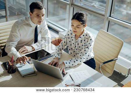 Creative Workers. The Top View Of Pleasant Young Colleagues Sitting At The Table And Developing The