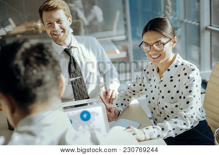Positive Ambience. Charming Cheerful Young Woman And Her Male Colleague Sitting In Their Boss Office
