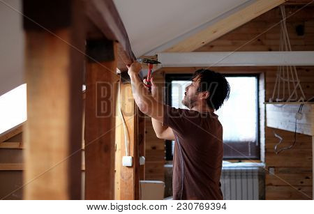 Man Building A House And Workimg With Hammer And Wood