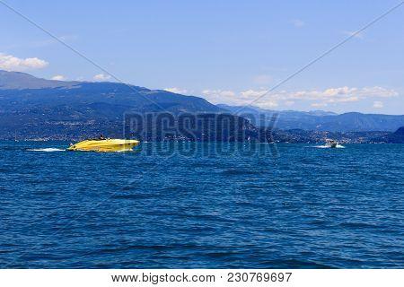 Motorboats Boating On Lake Garda With Mountain Panorama, Italy