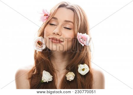 Gentle young woman 20s wearing makeup posing on camera with beautiful eustoma flowers in her long auburn hair and closed eyes isolated over white background