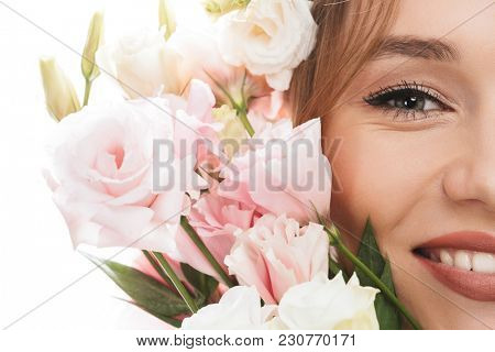 Beauty portrait closeup of charming girl 20s smiling and posing with blossom tulip gentian flowers at her face isolated over white background poster
