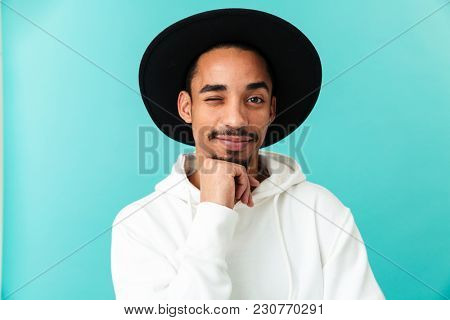 Portrait of a smiling young afro american man in hat looking at camera and winking isolated over blue background