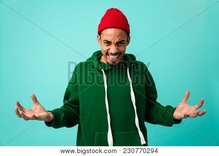 Portrait of a furious young afro american man in hat gesturing with hands isolated over blue background