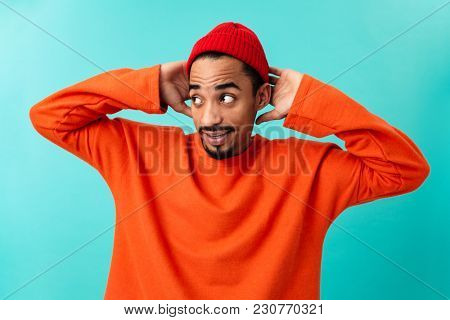 Portrait of a confused young afro american man in hat holding hands at his head isolated over blue background