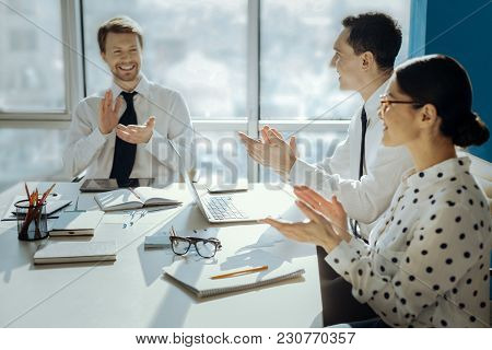 Great Accomplishment. Joyful Young Businesspeople Sitting At The Table In The Conference Room And Cl
