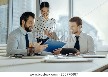 Close-knit Team. Upbeat Young Colleagues Carrying Out A Business Meeting In The Conference Room And