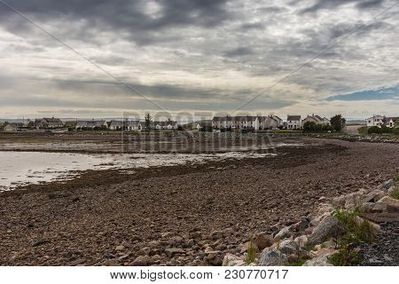 Aultbea, Scotland - June 9, 2012: Village Houses Behind Low Tide Bay Exposing Rocky Beach Under Heav