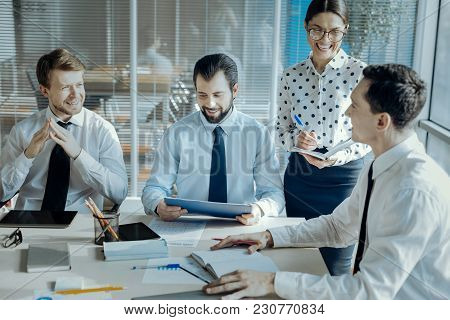 Upbeat Mood. Joyful Young Businesspeople Sitting At The Table In The Conference Room And Laughing Wh