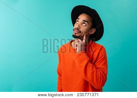 Portrait of a pensive young afro american man in hat looking away isolated over blue background
