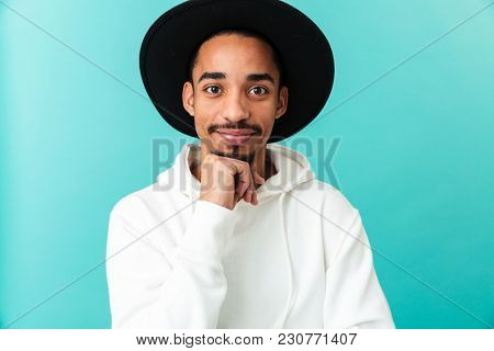 Portrait of a smiling young afro american man in hat looking at camera with hand on his chin isolated over blue background