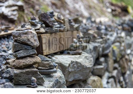 Stacks Of Rock Cairns Line A Retaining Wall On The Floyen Mountain Trail In Bergen, Norway.