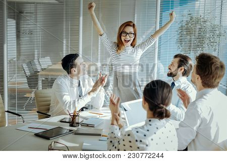 Exhilarating News. Upbeat Young Woman Celebrating Receiving Good News During The Meeting With Her Co