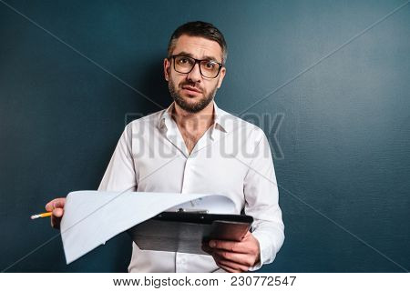 Image of displeased businessman standing over dark blue background looking camera holding documents.