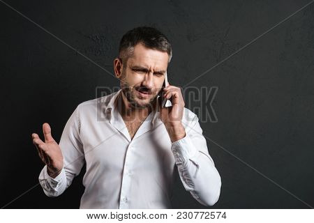 Image of displeased businessman isolated over dark black background talking by mobile phone.