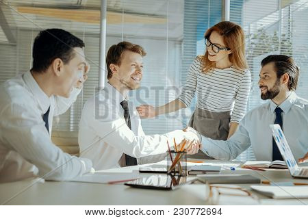 Problem Solved. Caring Female Team Leader Reconciling Her Two Male Colleagues During The Meeting And