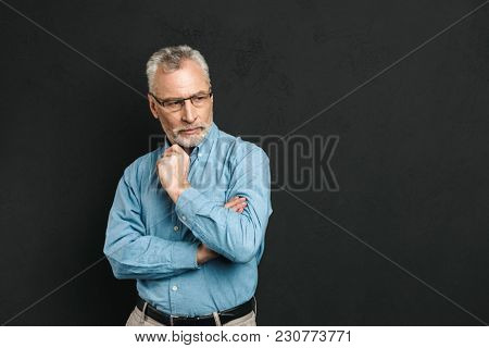 Portrait of a pensive mature man dressed in shirt looking away at copy space over black background
