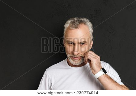 Image of handsome mature old man standing isolated over black wall. Looking camera.