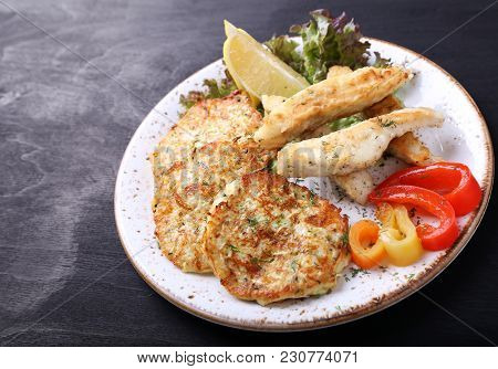 Fish With Zuccini Pancakes  And  Fresh Pepperon Dark Background