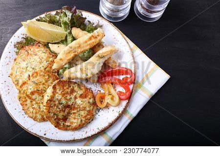 Fried Fish With Zuccini Pancakes  On Dark Background