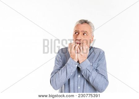 Frightened mature man in blue shirt looking up at copy space and afraid isolated over white