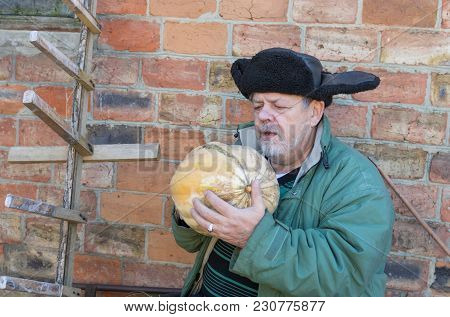 Outdoor Portrait Of A Bearded Ukrainian Peasant With Pumpkin Sitting Against Brick Wall