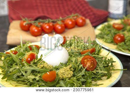 Italian Burrata Cheese With Arugula, Pesto Sauce And Cherry Tomatoes On A  Plate