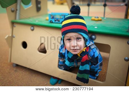 Beautiful Child Sits In Small House At The Playground Area. Serious Little Boy Playing In The Yard A