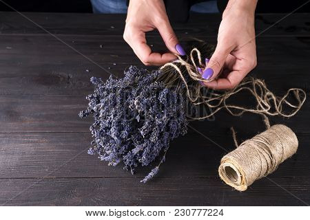Female Florist Tying Up Fresh Bouquet With Lavender On A Wooden Old Background