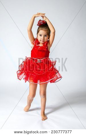 A Sweet, Little Girl In A Red Ballet Costume Poses With Hands Above Her Head On A White Background.