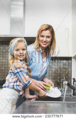 Little Daughter And Mother Looking At Camera While Washing Dishes After Dinner Together At Home