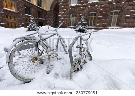 Two Bicycles Adult And Child Chained To The Counter Outside, Covered With Snow During The Snow